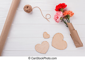 Colorful flowers, heart shaped wood and thread.