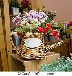 Colorful flowers in rattan watering can on wooden table