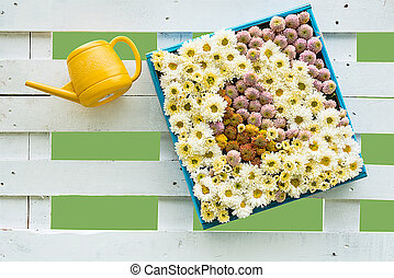 Colorful flowers on a blue wooden frame with yellow watering pot on a white fence wooden.