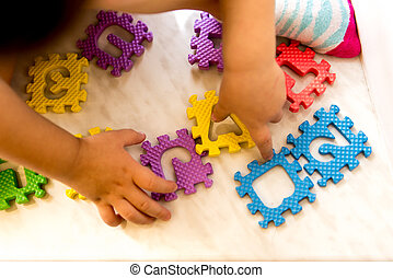 Colorful foam puzzle letters and numbers in kid's hands on a light table