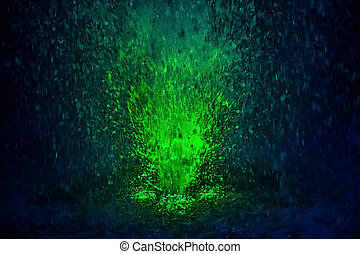 Colorful fountain splashes green color of water drops on a ...