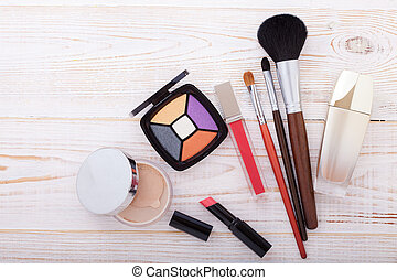 Colorful frame with various makeup products on white wooden background