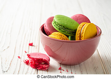 Colorful french macarons in bowl on white wooden background