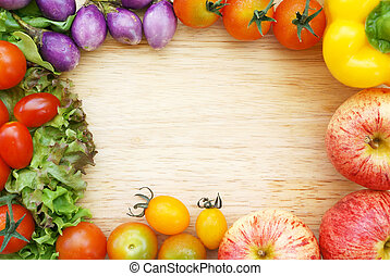 Colorful fresh organic vegetables composing a frame on a wooden chopping board