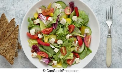 Colorful fresh vegetable salad with feta cheese in a white ...