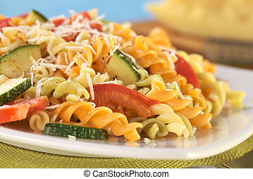 Colorful fusilli pasta with zucchini, tomato and grated cheese (Selective Focus, Focus on the tomato in front)