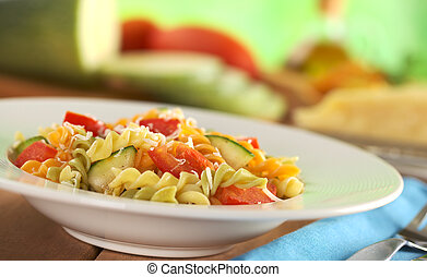 Colorful fusilli pasta with zucchini, tomato and grated cheese with fork on the side and ingredients in the back (Selective Focus, Focus one third into the meal)