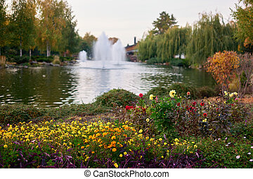 Colorful garden flowers in front of a pond.
