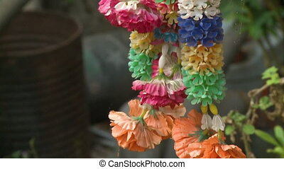A hand held, tilting, close up shot of colorful garlands ready to be worn.