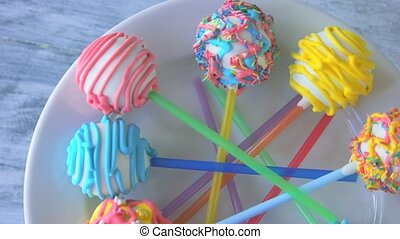 Colorful glazed sweets on sticks. Delicious biscuits with colorful frosting. Baked lollipops for kids party.