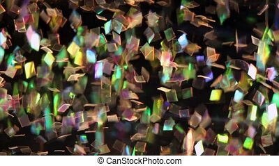 Colorful mylar glitter floats in water, traveling on the water's current.