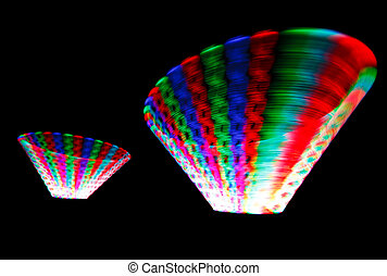 Colorful glowing trail rotating LED, in form of two cones on black background.