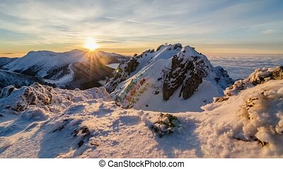 Colorful golden sunset in snowy mountains in winter above mist clouds. Dolly shot time lapse day to night