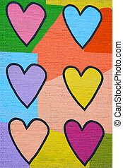 Colorful graffiti spray painted funny hearts on the decorated  brick wall - makes a great background or backdrop