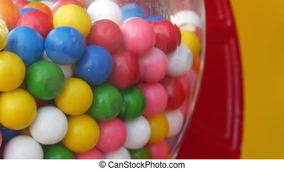 Colorful gumballs in classic vending machine, USA. Multi colored buble gums, coin operated retro dispenser. Chewing gum candies as symbol of childhood and summertime. Mixed sweets in vintage automate.