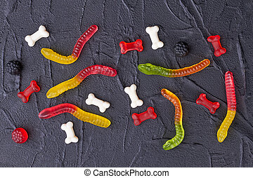 Colorful gummy candies on black background.