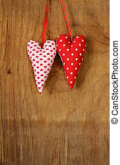 colorful handmade fabric hearts on a wooden background