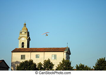 colorful hang glider in the air, over a church
