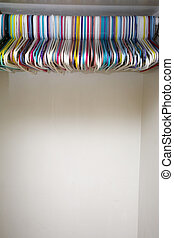 Colorful hangers in empty white closet
