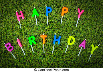 Colorful happy birthday candles on field