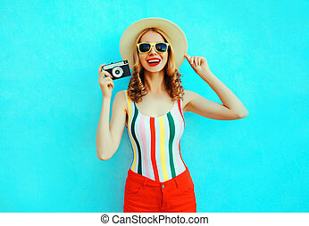 Colorful happy smiling young woman holding retro camera in summer straw hat having fun on blue wall background