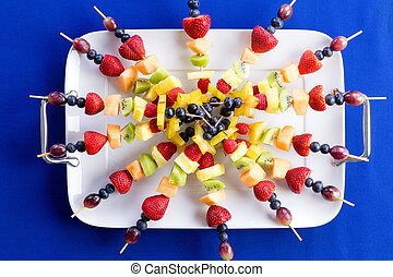 Colorful healthy fruit kebabs on a tray