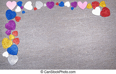 colorful hearts of glitter of all colors on a gray granite background. Concept of valentines day and love in general