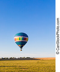 Colorful hot-air balloon flying over the forest