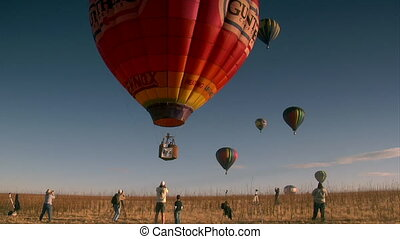 colorful hot air balloon liftoff with spectators taking...
