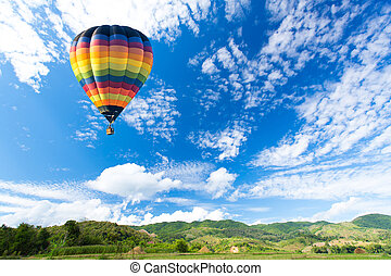 Colorful hot air balloon over green field