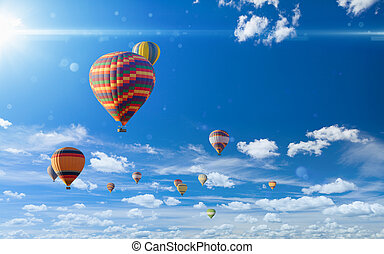 Colorful hot air balloons flying in blue sky with white clouds and bright sun light