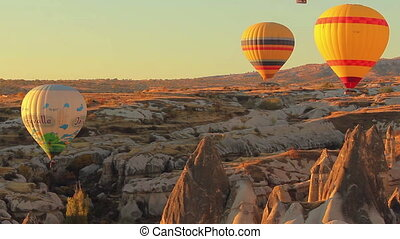 Colorful hot air balloons flying over valleys in Goreme, Cappadocia, Turkey.