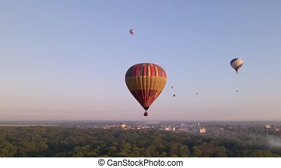 Colorful hot air balloons flying over green park in small ...