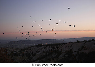 Colorful hot air balloons flying over mountains.