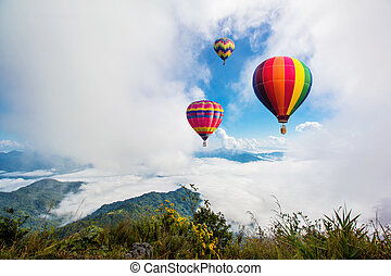 Colorful hot-air balloons flying over the mountain at Pha Tung, Chiangrai province ,North of Thailand.