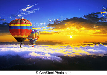Colorful hot air balloons flying over the mountain covered by morning fog at sunrise.