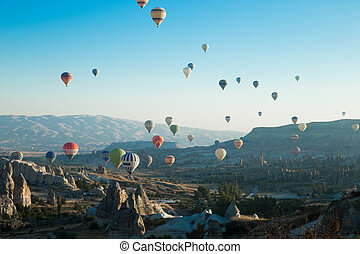 air balloons flying over the valley at Cappadocia
