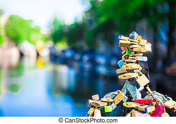 Colorful hundreds of padlocks-love locks on canal in Amsterdam, Netherlands