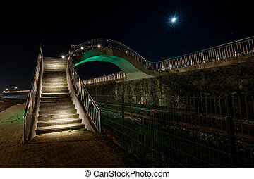 Colorful illuminated walkway in Harlingen with strap and metal silver balustrade in an organic curve shape.