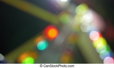 Colorful illumination of attraction at fun fair, defocus -...