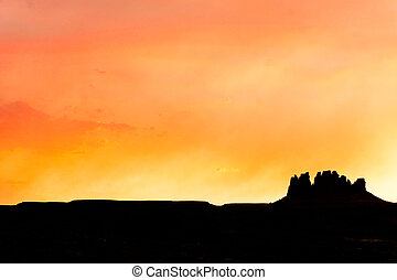 colorful intense sunset sky over a silhouette of a lone mesa rock formation
