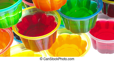 Colorful jellies in plastic bowls arranged in a pile and photographed from above (Selective Focus, Focus on the rim of the left red jelly)