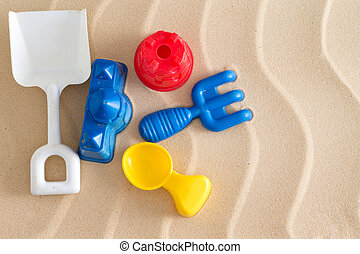 Colorful kids plastic toys at the beach with a spade, fork , spoon and two little moulds on golden sea sand with a decorative wavy pattern and copyspace