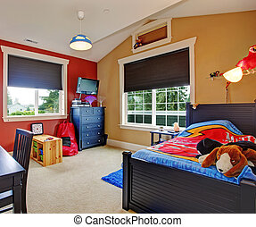 Colorful kids room with beige and red walls. Furnished with single bed and desk