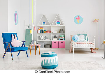 Patterned pouf near blue armchair in colorful kid's room interior with poster above white bed