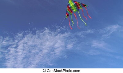 Colorful Kite Flying in Blue Cloudy Sky