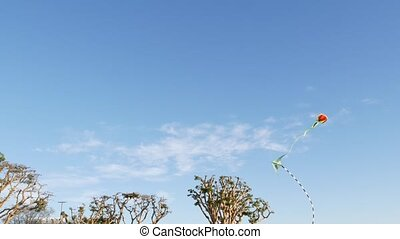 Colorful kite flying in blue sky over trees in Embarcadero Marina park, San Diego, California USA. Kids multi colored toy gliding mid-air in wind. Symbol of childhood, summertime and leisure activity.