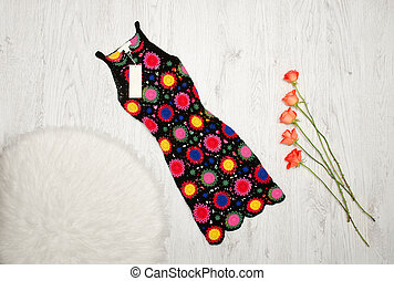 Colorful knitted dress and orange roses on a wooden background. Fashionable concept, top view
