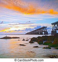 Colorful landscape of a beautiful tropical sunset or sunrise. Taken at Bahia Honda Key State Park in Florida. Old Flagler Bridge remains as a tourist landmark and a monument to a hurricane.