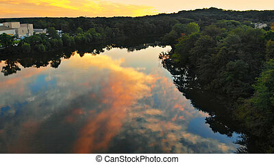 Colorful landscape of river near a forest under a beautiful sky with bright clouds during sunset